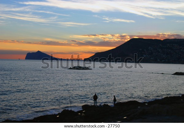 fishermen on the rocks at sunset on the beach at Calpe in southern spain