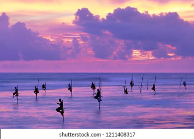 Fishermen on stilts in silhouette at the sunset in Galle, Sri Lanka