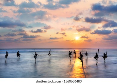 Fishermen on the stilts in silhouette at the sunset in Sri Lanka.