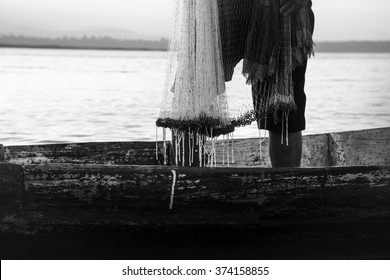 The fishermen on wooden boat,he casting  for catching fish at lake in sunrise time,thailand (The casting people living along the River)