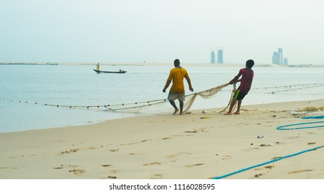 Fishermen reeling in a big net at the Oniru Beach, Victoria Island, Lagos / Nigeria - June 16th 2018
