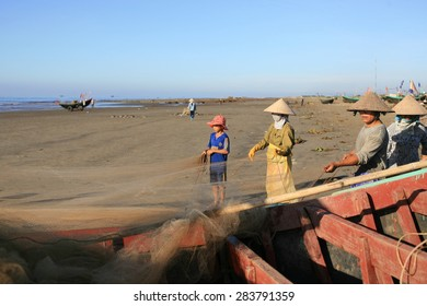 Fishermen remove fish from fishing nets at beaches HAILY, NAMDINH, VIETNAM Aug 1, 2014. Fishing is a traditional craft in Vietnam