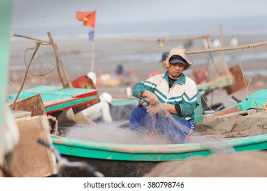Fishermen repairing nets on a boat trip out to sea in the afternoon Feb 21, 2016 at the beach of Hai Ly, Vietnam.