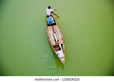 Fishermen riding on a traditional boat in the river unique photo