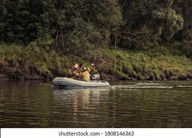 Pêcheurs naviguant sur un bateau gonflable le long de la rive de la rivière et pêchant avec des bâtons de pêche