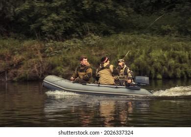 Pêcheurs naviguant sur un bateau à moteur gonflable le long de la rive de la rivière et pêchant avec des bâtons de pêche