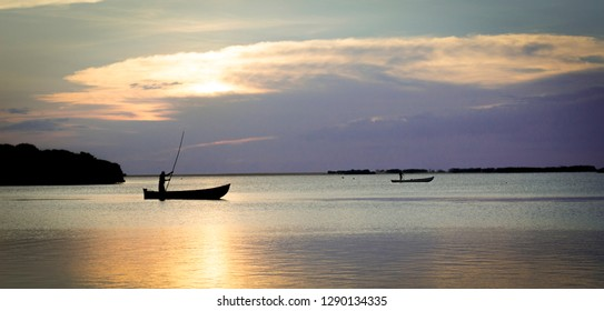 Fishermen silhouette at sunset, punting their boat past the sri lankan coast