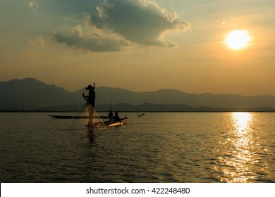 Fishermen, silhouette,Fishermen silhouette lifestyle in action when fishing in the Freshwater ponds(kwan phayao) Phayao, Thailand. Landscape ,Outdoor, Silhouette,Twilight River.