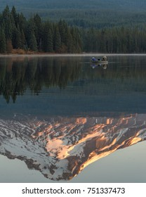 Fishermen in a small boat on Trillium Lake at sunrise as the mountain basks in the glowing reflection in the foreground.