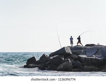 Fishermen standing on rocks by the ocean