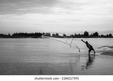 Fishermen throw a fishing net to catch fishes.