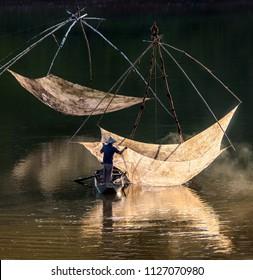 Fishermen throw a fishing nets. Bridge survey. Evening view. Da Lat city, Vietnam