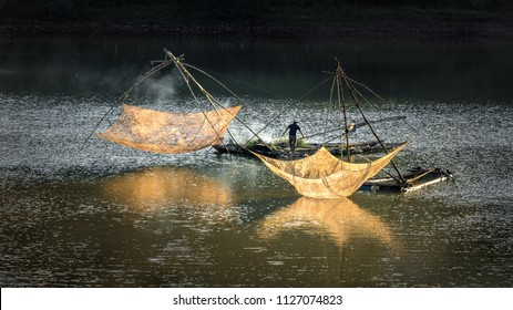 Fishermen throw a fishing nets. Bridge survey. Evening view. Da Lat city, Vietnam