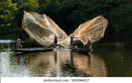 Fishermen throw a fishing nets. Morning view. Hue city, Northern Vietnam