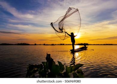fishermen throwing net fishing in lake on morning sunrise