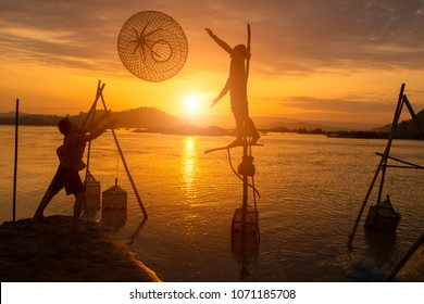 Fishermen working time with friend on Mekong river the during sunrise between Thailand - Laos. This is the culture in basin Mekong of Asian.