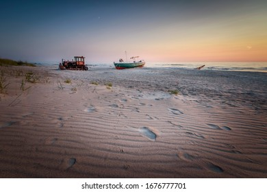 Fishermens boat on the beach with old bulldozer in front with steps on beach