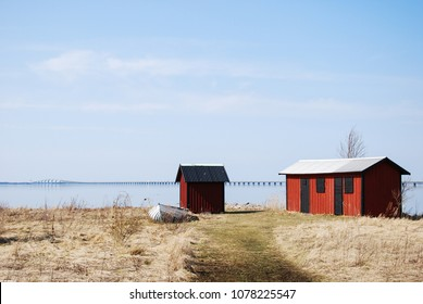 Fishermens old red cabins in front of the landmark The Oland Bridge crossing a strait in the Baltic Sea in Sweden