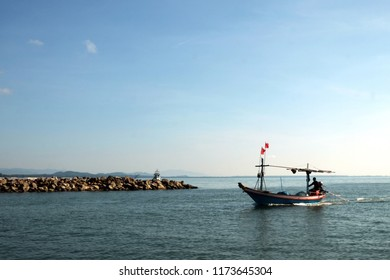 fishery boat heading inn of harbor at evening. Background are the clear blue sky and the sea.