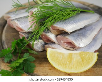 fishes herrings with lemon on a chopping board
