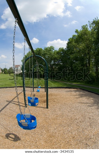 Fisheye lens captured view down a row of swings on the playground.