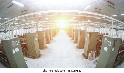 Fisheye lens effect:A neat row of spinning machine production line, backlight effect. Background of modern textile industry.