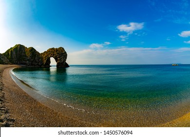 Fisheye lens shot of Durdle Door with nicely blurred calm sea water during sunrise