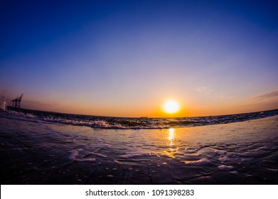 Fisheye perspective sea view at the sunrise. Sun and sky reflected on the ground. Morning seascape. Concept of piece and calmful rest