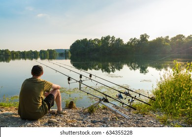 Fishing adventures, carp fishing. Angler is fishing with carpfishing technique in freshwater, in a beautiful summer day