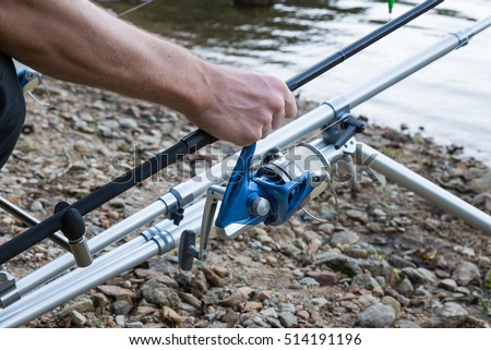 Fishing adventures - Carp fishing, closeup of a hand grasping a fishing rod with reel