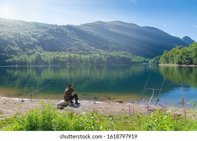 Fishing adventures, carp fishing. Man fishing on lake. Concept of patience, waiting, relaxation and healthy lifestyle in the nature