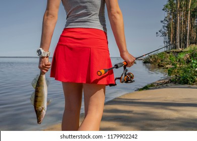 Fishing. Back view of sexy girl with walleye zander fish trophy at lake shore