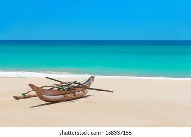 Fishing boat at beautiful sandy ocean palm beach, Indian Ocean