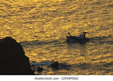 A fishing boat beneath the sunset. Kalymnos island, Greece.