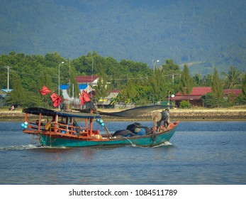 A fishing boat chugs up the Preak Tuek Chhu River in Kampot Cambodia