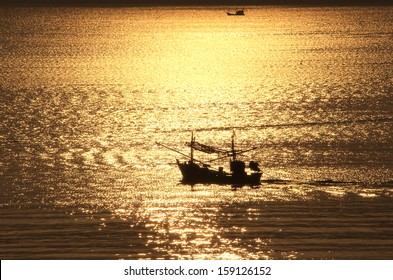 A fishing boat is coming home in the early morning at sunrise from the work of the night in Prachuab, Thailand. It crosses the the golden reflection of the rising sun in the water of the sea.