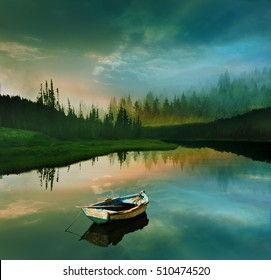 fishing boat docked in calm lake of a dreamy landscape with beautiful misty mountain during sunset