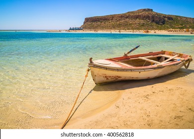 Fishing boat docked to coast on the beautiful beach of Crete, Greece.