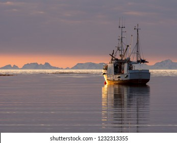 A fishing boat during sunset outside Bodø in Norway with the mountains of Lofoten in the background.