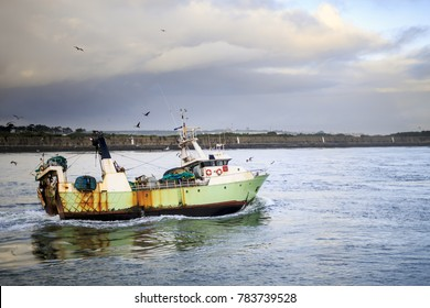 Fishing boat entering harbor after a day fishing on the sea with heavy clouds