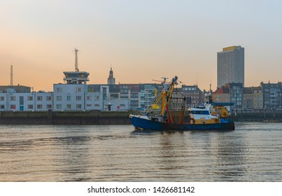 Fishing boat entering the harbor of Ostend at sunset with a cityscape of the city with its highest skyscraper, West Flanders, Belgium.