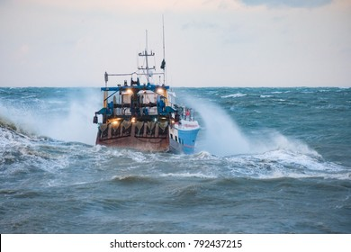 Fishing boat facing strong waves on its way out to Sea from Port en Bessin in Normandy, France.