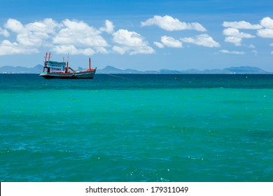 A fishing boat is floating in the blue sea with clear sky