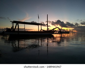 Fishing boat floating on sea at early morning. Beautiful sunrise colors and the morning light scenery. Tranquility nature landscape scene. Sanur Beach, Bali, Indonesia.