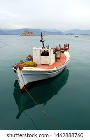 A fishing boat floating in the pretty harbor in Nafplio with Bourtzi Castle. Nafplio is an old town in Peloponnese Greece with historic roots. Nafplio is also known as Nafplion, Nauplio and Nauplion.