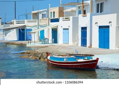 Fishing boat in front of a blue fishing village in Milos island in Greece