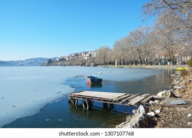 Fishing boat in frozen lake Orestiada, old wooden pier and Kastoria city as background