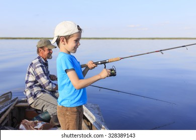Fishing boat. Grandfather and grandson fishing together on a spinning sitting in a boat on a river