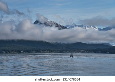 Fishing boat heading back to Juneau Alaska with clouds over the mountains.