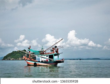 The fishing boat is heading to the sea in the morning on the beautiful background of blue sky with white clouds, sea and mountain, Chumphon province Southern Thailand.